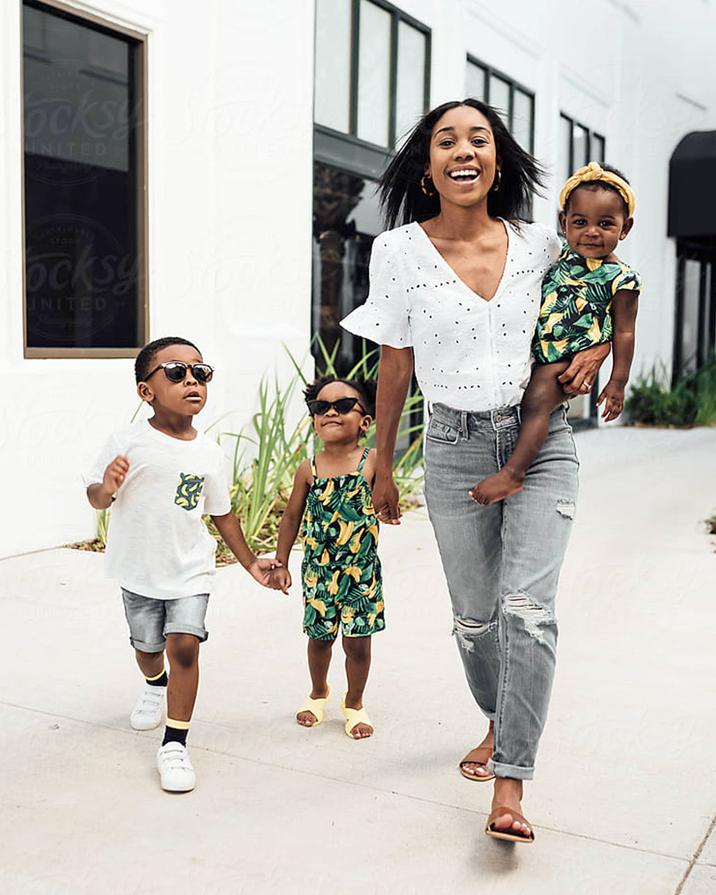 mom walking with three young children