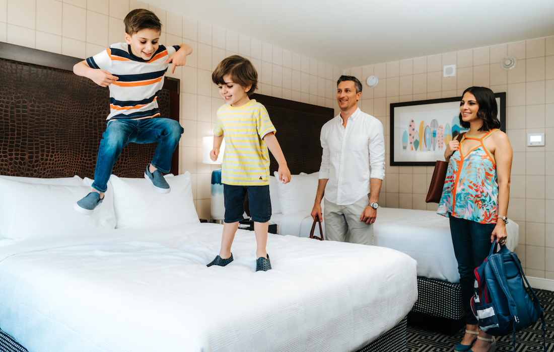 Two boys jumping on bed at Hotel Lulu