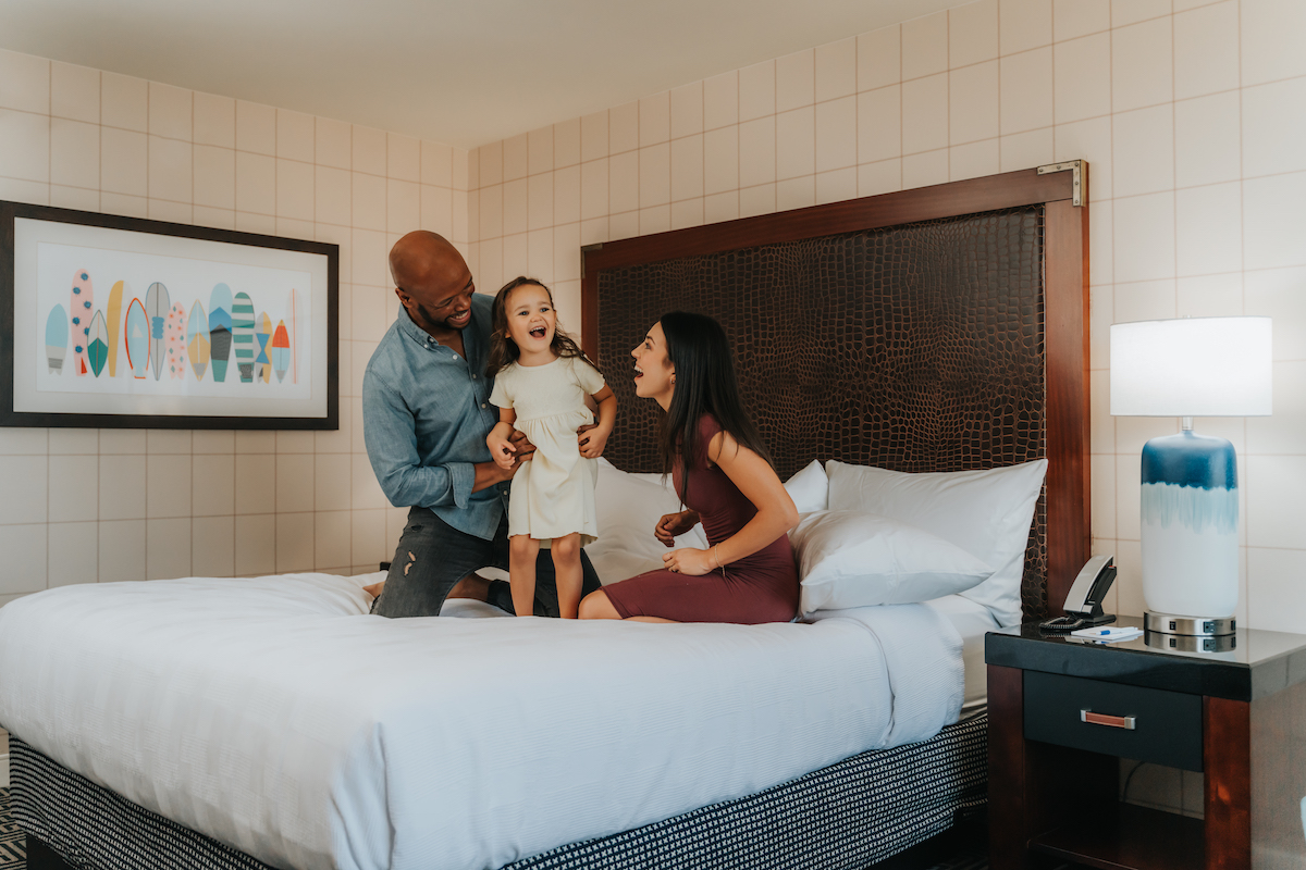 Family sitting on hotel bed laughing
